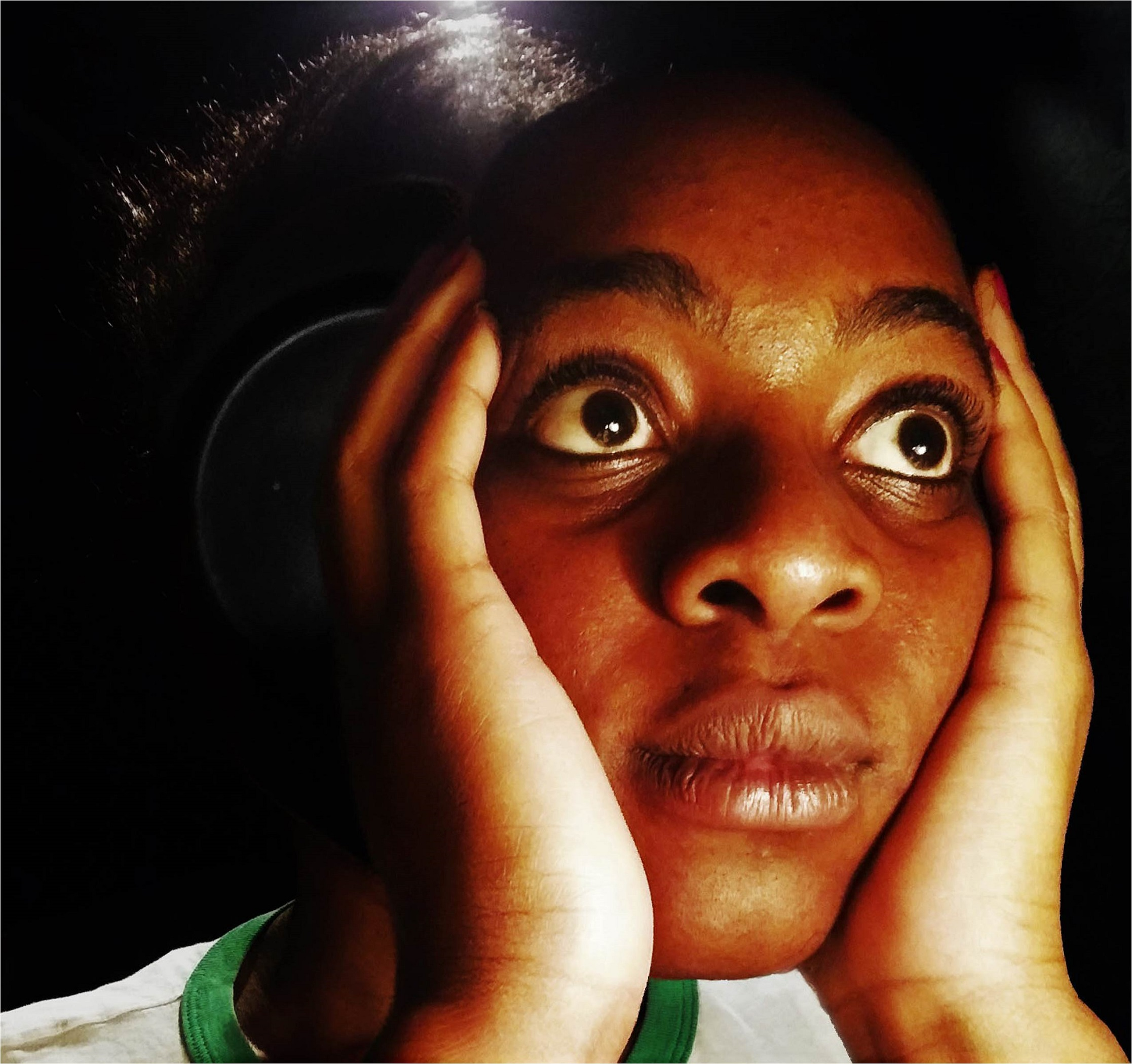 Black woman with hands on her face looking into distance