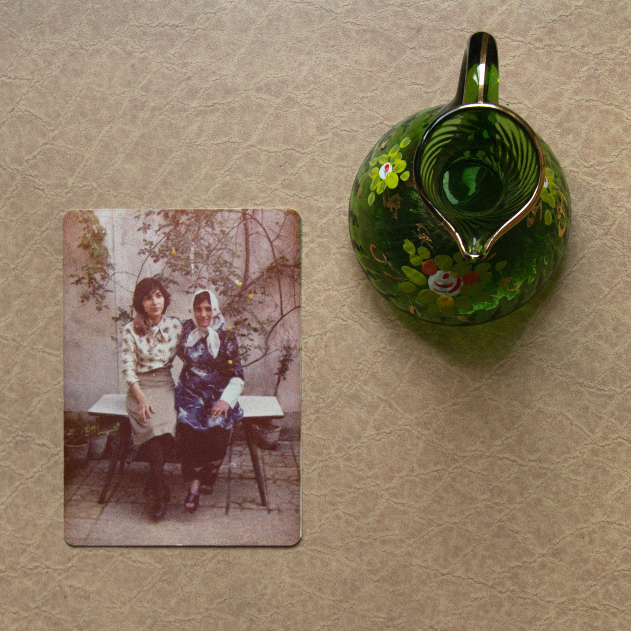 Photo of two woman on a table and a green glass teapot next to it.