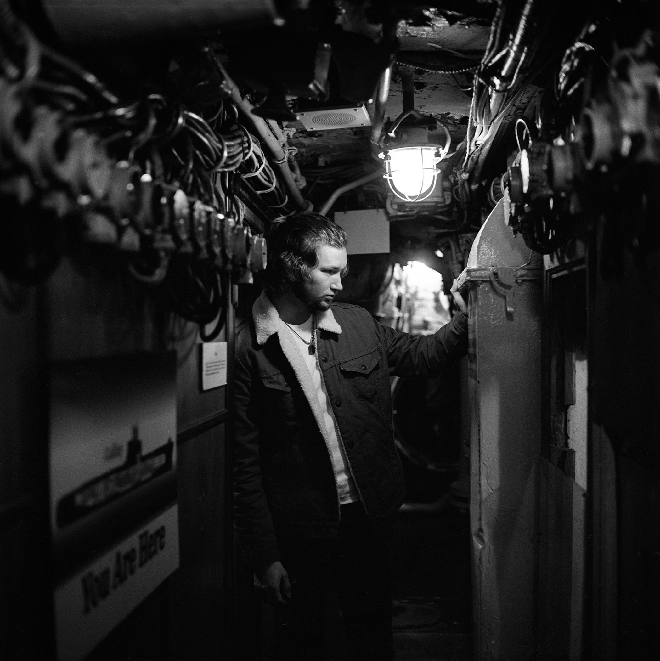 Black and white photo of a person in a dark mechanical hallway