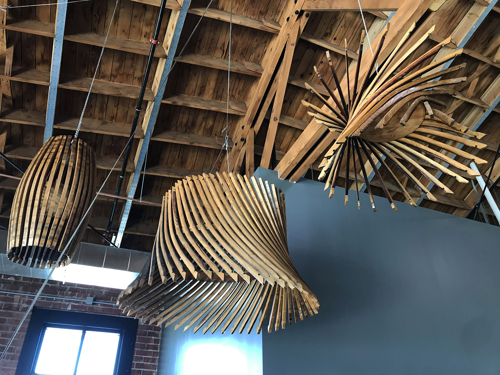 Reclaimed Oak Wine Barrels crafted into sculpture hanging from ceiling