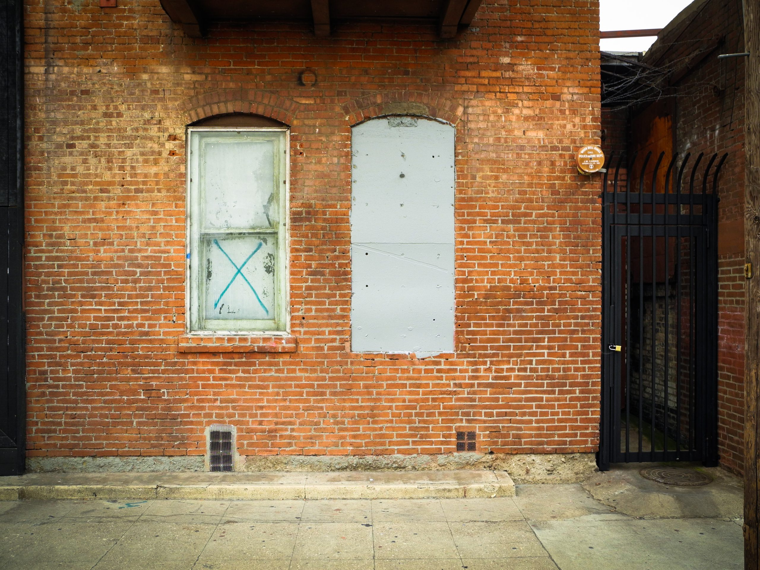 a brick wall with two windows that are shut closed